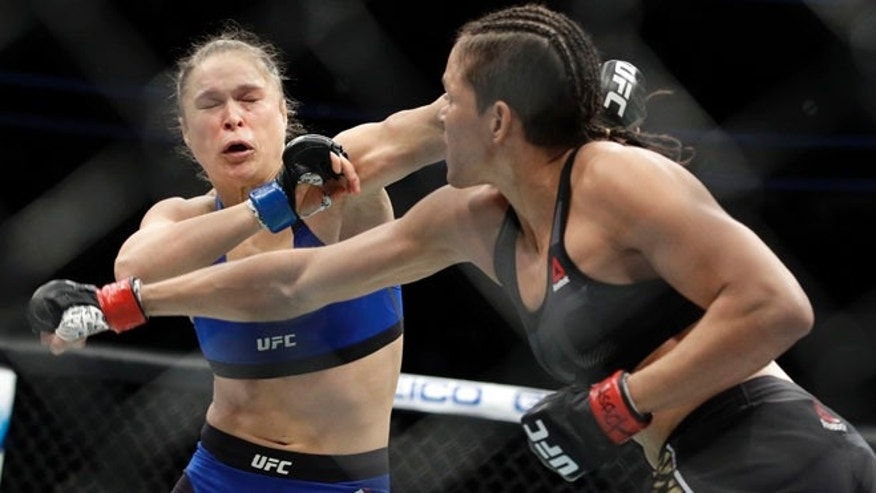 Amanda Nunes, right, throws a punch at Ronda Rousey in the first round of their women's bantamweight championship mixed martial arts bout at UFC 207, Friday, in Las Vegas.