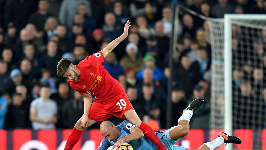 Liverpool's Adam Lallana, top, and Manchester City's Pablo Zabaleta battle for the ball during the English Premier League soccer match Liverpool against Manchester City at Anfield, Liverpool, England, Saturday, Dec. 31, 2016. (Dave Howarth/PA via AP)