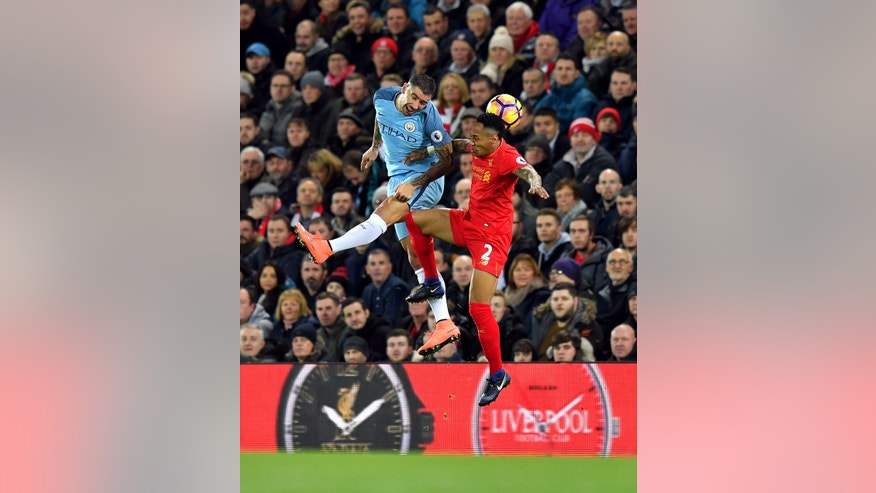 Manchester City's Aleksandar Kolarov, left, and Liverpool's Nathaniel Clyne battle for the ball in the air during the English Premier League soccer match Liverpool against Manchester City at Anfield, Liverpool, England, Saturday, Dec. 31, 2016. (Dave Howarth/PA via AP)