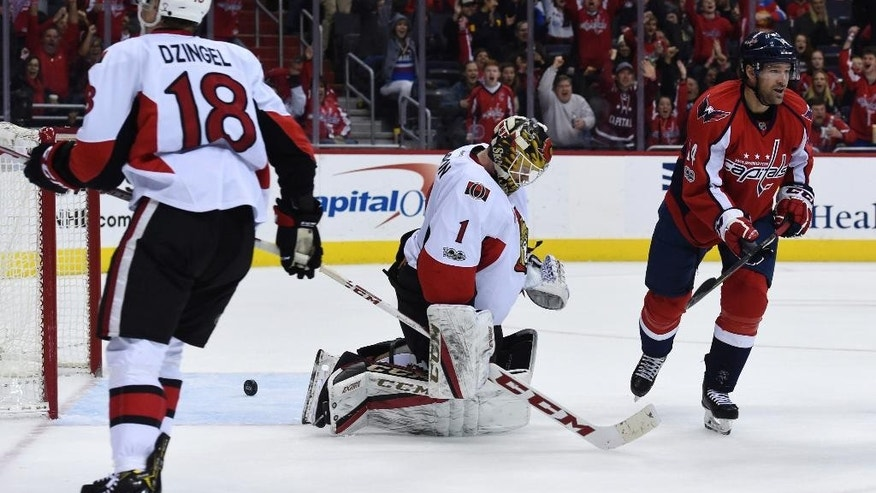 Ottawa Senators goalie  Mike Condon (1) reacts after a goaly Washington Capitals defenseman Karl Alzner, not seen, in front of Capitals right wing Justin Williams (14) and Senators left wing  Ryan Dzingel (18) during the second period of an NHL hockey game, Sunday, Jan. 1, 2017, in Washington. (AP Photo/Molly Riley)