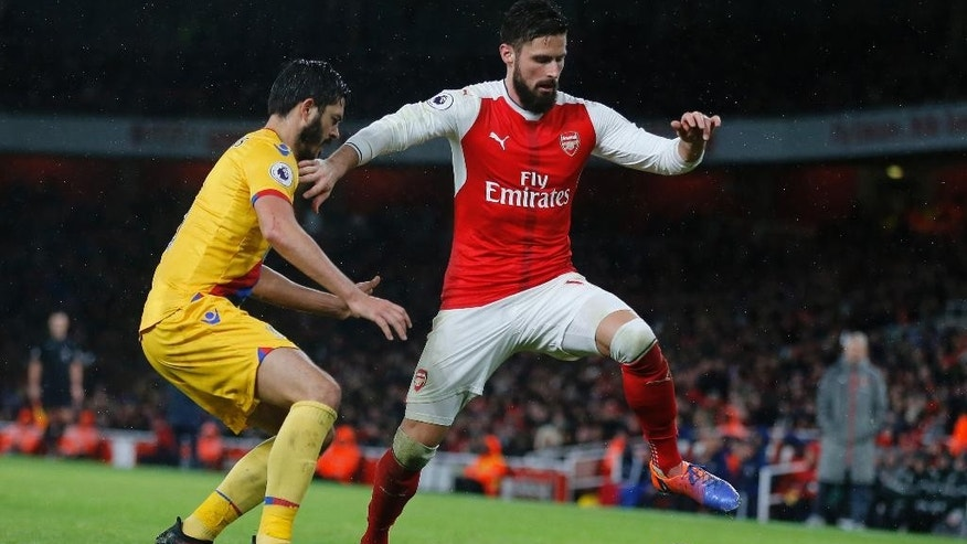 Crystal Palace's James Tomkins, left, and Arsenal's Olivier Giroud challenge for the ball during the English Premier League soccer match between Arsenal and Crystal Palace at the Emirates stadium in London, Sunday, Jan. 1, 2017.(AP Photo/Frank Augstein)