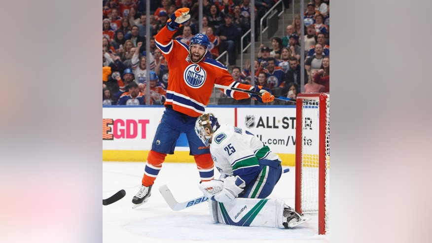 Edmonton Oilers' Patrick Maroon (19) celebrates a teammate's goal against Vancouver Canucks goalie Jacob Markstrom (25) during the second period of an NHL hockey game Saturday, Dec. 31, 2016, in Edmonton, Alberta. (Jason Franson/The Canadian Press via AP)