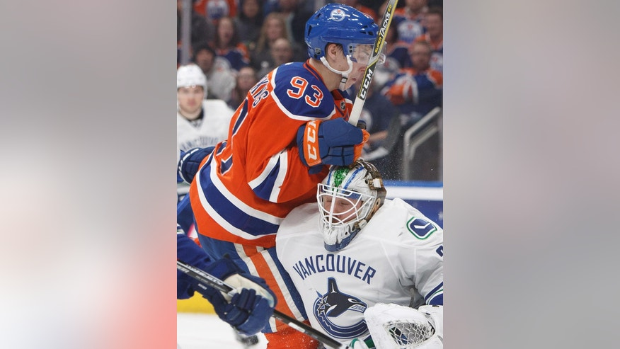 Edmonton Oilers' Ryan Nugent-Hopkins (93) crashes into Vancouver Canucks goalie Jacob Markstrom during the second period of an NHL hockey game Saturday, Dec. 31, 2016, in Edmonton, Alberta. (Jason Franson/The Canadian Press via AP)