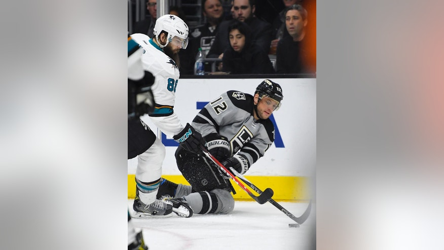 CORRECTS TO SECOND PERIOD - Los Angeles Kings right wing Marian Gaborik, right, of Slovakia, passes the puck while under pressure from San Jose Sharks defenseman Brent Burns during the second period of an NHL hockey game, Saturday, Dec. 31, 2016, in Los Angeles. (AP Photo/Mark J. Terrill)