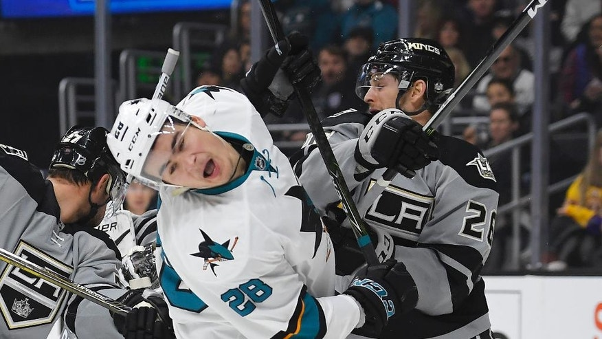 San Jose Sharks right wing Timo Meier, center, of Switzerland, takes a hit from Los Angeles Kings center Nic Dowd during the first period of an NHL hockey game, Saturday, Dec. 31, 2016, in Los Angeles. (AP Photo/Mark J. Terrill)