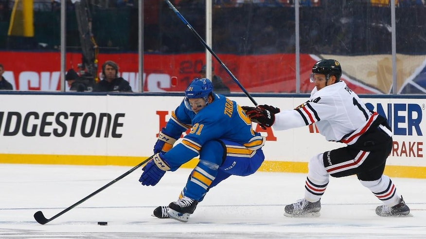 St. Louis Blues' Vladimir Tarasenko, left, of Russia, reaches for the puck as he is pressured by Chicago Blackhawks' Richard Panik, of Slovakia, during the second period of the NHL Winter Classic hockey game at Busch Stadium, Monday, Jan. 2, 2017, in St. Louis. (AP Photo/Billy Hurst)
