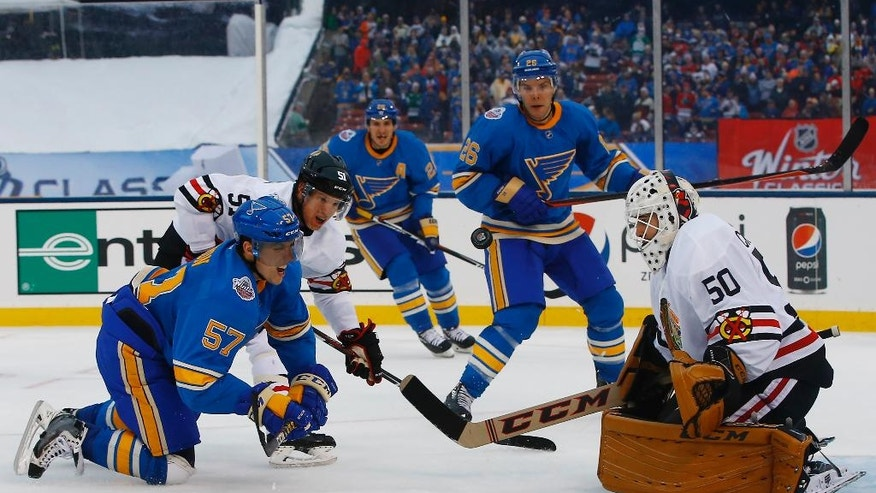 St. Louis Blues' David Perron, left front, is checked to the ice by Chicago Blackhawks' Brian Campbell, second from left, after taking a shot against Blackhawks goalie Corey Crawford, right, during the second period of the NHL Winter Classic hockey game at Busch Stadium, Monday, Jan. 2, 2017, in St. Louis. (AP Photo/Billy Hurst)