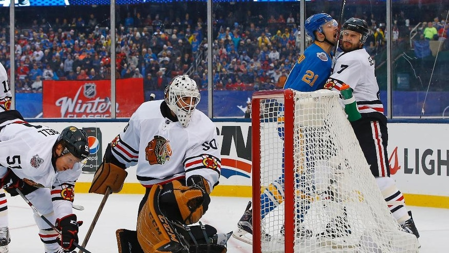 Chicago Blackhawks' goalie Corey Crawford, center, looks back after giving up a goal to St. Louis Blues' Patrik Berglund, third from left, of Sweden, as Blackhawks' Brian Campbell, left, and Brent Seabrook, right, look on during the second period of the NHL Winter Classic hockey game at Busch Stadium, Monday, Jan. 2, 2017, in St. Louis. (AP Photo/Billy Hurst)