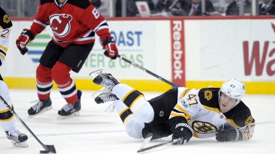 Boston Bruins' Torey Krug (47) hits the ice after being tripped by New Jersey Devils' Beau Bennett (8) during the first period of an NHL hockey game Monday, Jan. 2, 2017, in Newark, N.J. (AP Photo/Bill Kostroun)