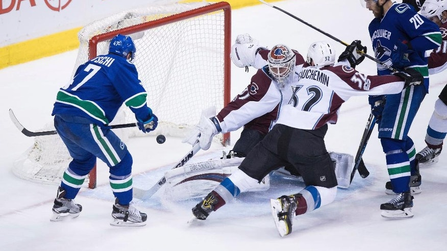 Vancouver Canucks' Sven Baertschi, left, scores a goal against Colorado Avalanche goalie Calvin Pickard, center, as Francois Beauchemin, center right, checks Canucks' Brandon Sutter during the third period of an NHL hockey game in Vancouver, British Columbia, Monday, Jan. 2, 2017. Baertschi scored twice, including the winner on a power play with under four minutes to go in the third period. (Darryl Dyck/The Canadian Press via AP)