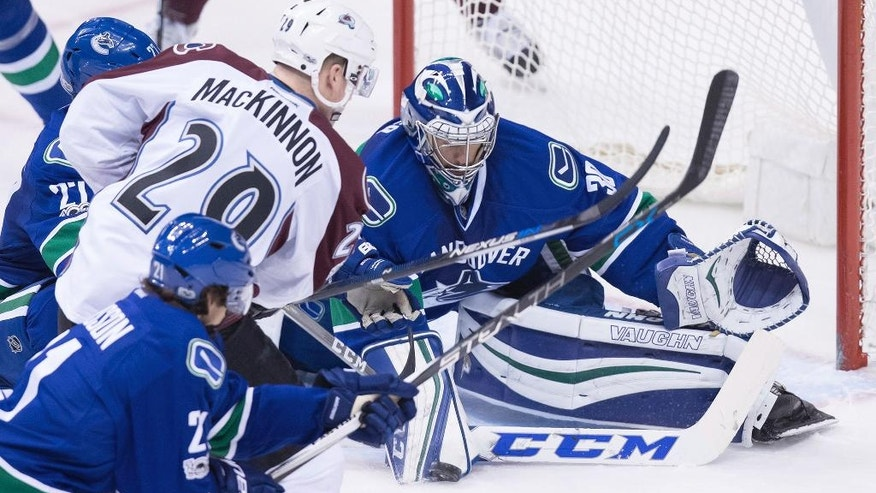 Vancouver Canucks' goalie Ryan Miller, back, stops Colorado Avalanche's Nathan MacKinnon during the third period of an NHL hockey game in Vancouver, British Columbia, Monday, Jan. 2, 2017. (Darryl Dyck/The Canadian Press via AP)