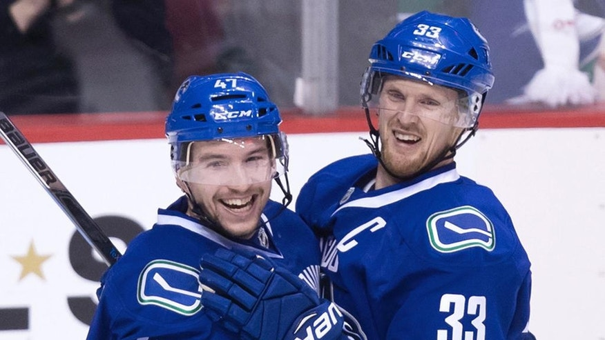 Vancouver Canucks' Sven Baertschi, left, and Henrik Sedin, of Sweden, celebrate Baertschi's second goal against the Colorado Avalanche during the third period of an NHL hockey game in Vancouver, British Columbia, Monday, Jan. 2, 2017. Baertschi scored twice, including the winner on a power play with under four minutes to go in the third period. Vancouver won, 3-2. (Darryl Dyck/The Canadian Press via AP)