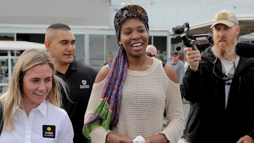 United States' Venus Williams, center, is escorted to a car on her arrival at Auckland Airport in New Zealand, Friday, Dec. 30, 2016. Williams is in New Zealand for the ASB Classic tennis tournament which starts on Monday, Jan. 2, 2017. (Michael Craig/New Zealand Herald via AP)
