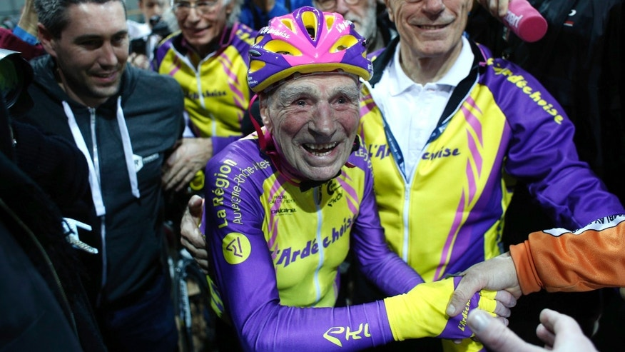 French cyclist Robert Marchand, 105, is cheered after setting a record for distance cycled in one hour, at the velodrome of Saint-Quentin en Yvelines, outside Paris, Wednesday, Jan. 4, 2017. The Frenchman set a world record in the 105-plus age category -- created especially for the tireless veteran -- by riding 22.547 kilometers in one hour. (AP Photo/Thibault Camus)