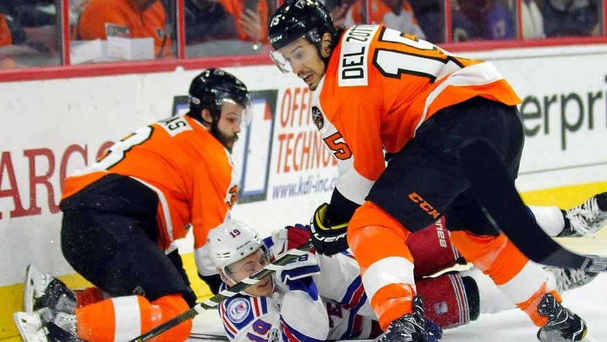 Philadelphia Flyers' Radko Gudas, left, Michael Del Zotto, right, keep the puck away from New York Rangers' Jesper Fast, center, during the first period of an NHL hockey game, Wednesday, Jan. 4, 2017, in Philadelphia. (AP Photo/Tom Mihalek)