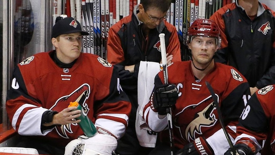FILE - In this Feb. 15, 2016, file photo, Arizona Coyotes backup goalie Nathan Schoenfeld, left, signed to the team only hours prior to the game due to an injury to goalie Anders Lindback, sits next to Shane Doan during the second period of an NHL hockey game, in Glendale, Ariz. Hockey is the only professional sport where someone can go from being a fan to suiting up in the NHL. Injuries and illnesses to goaltenders have opened the door for anyone from equipment managers to Zamboni drivers and amateur coaches to dress or even play goal in an NHL game. (AP Photo/Ross D. Franklin, File)