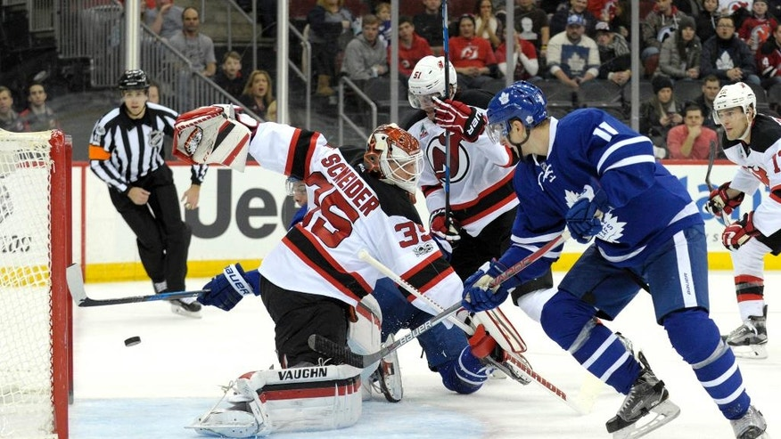 Toronto Maple Leafs' Auston Matthews, rear, scores a goal behind New Jersey Devils goaltender Cory Schneider as Maple Leafs' Zach Hyman, right, looks on during the first period of an NHL hockey game Friday, Jan. 6, 2017, in Newark, N.J. (AP Photo/Bill Kostroun)
