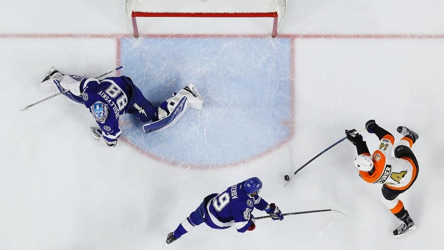 Philadelphia Flyers' Sean Couturier (14) scores a goal against Tampa Bay Lightning's Andrei Vasilevskiy (88) as Nikita Nesterov (89) defends during the second period of an NHL hockey game, Saturday, Jan. 7, 2017, in Philadelphia. (AP Photo/Matt Slocum)