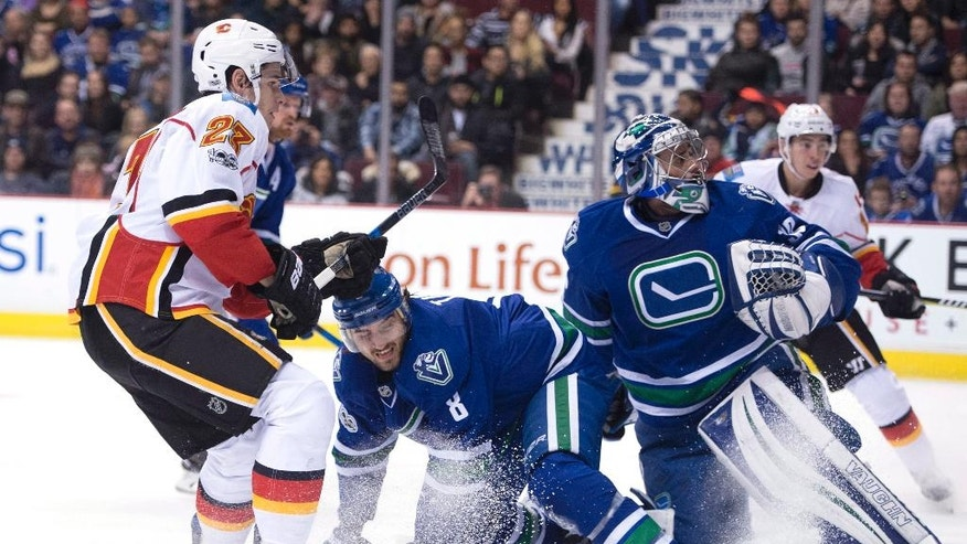 Vancouver Canucks defenseman Christopher Tanev (8) tries to stop Calgary Flames center Sean Monahan (23) from getting a shot on Vancouver Canucks goalie Ryan Miller (30) during the first period of an NHL hockey game, Friday, Jan. 6, 2017 in Vancouver, British Columbia.  (Jonathan Hayward/The Canadian Press via AP)
