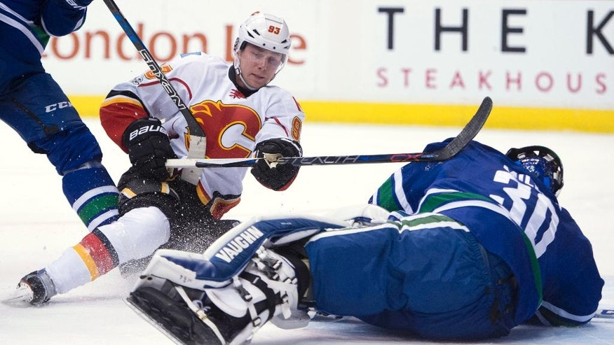 Calgary Flames center Sam Bennett (93) tries to get a shot past Vancouver Canucks goalie Ryan Miller (30) during the first period of an NHL hockey game, Friday, Jan. 6, 2017 in Vancouver, British Columbia.  (Jonathan Hayward/The Canadian Press via AP)