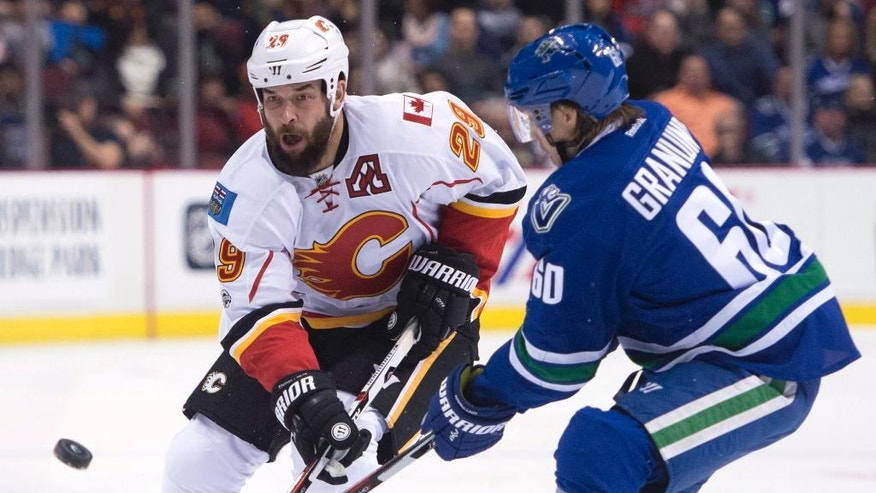 Vancouver Canucks center Markus Granlund (60) fights for control of the puck with Calgary Flames defenseman Deryk Engelland (29) during first-period NHL hockey game action in Vancouver, British Columbia, Friday, Jan. 6, 2017. (Jonathan Hayward/The Canadian Press via AP)
