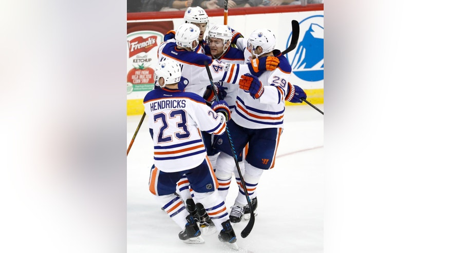 Edmonton Oilers players surround Mark Letestu, center, after he scored the game winning goal against the New Jersey Devils during overtime of an NHL hockey game, Saturday, Jan. 7, 2017, in Newark, N.J. The Oilers won 2-1 in overtime. (AP Photo/Julio Cortez)