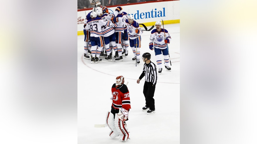 New Jersey Devils goalie Cory Schneider, bottom, skates away as Edmonton Oilers celebrate a goal by Mark Letestu during overtime of an NHL hockey game, Saturday, Jan. 7, 2017, in Newark, N.J. The Oilers won 2-1 in overtime. (AP Photo/Julio Cortez)