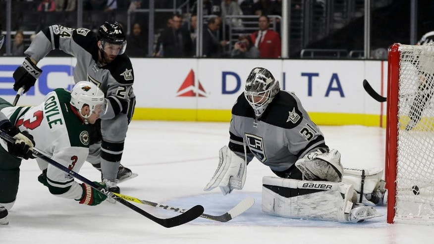Minnesota Wild center Charlie Coyle, left, scores past Los Angeles Kings goalie Peter Budaj, right, as defenseman Derek Forbort looks on during the first period of an NHL hockey game in Los Angeles, Saturday, Jan. 7, 2017. (AP Photo/Chris Carlson)