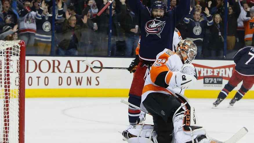 Columbus Blue Jackets' Sam Gagner, top, celebrates their goal against Philadelphia Flyers' Steve Mason during the overtime period of an NHL hockey game Sunday, Jan. 8, 2017, in Columbus, Ohio. The Blue Jackets beat the Flyers 2-1 in overtime. (AP Photo/Jay LaPrete)