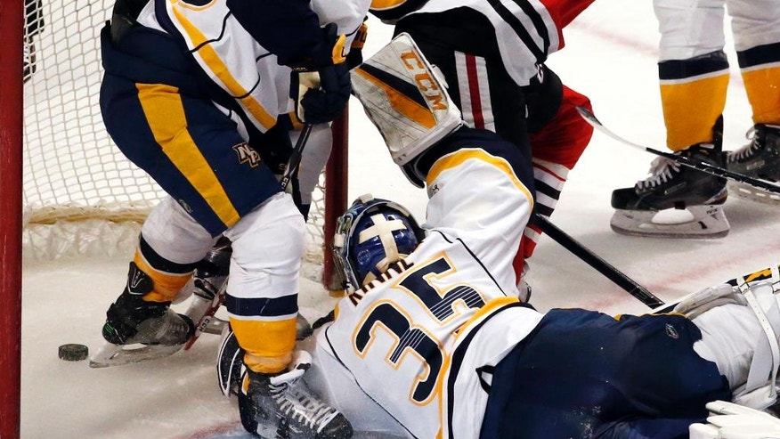 Nashville Predators goalie Pekka Rinne (35), left wing Kevin Fiala (56) and defenseman Yannick Weber (7) fail to save a shot by Chicago Blackhawks right wing Ryan Hartman during the third period of an NHL hockey game Sunday, Jan. 8, 2017, in Chicago. (AP Photo/Nam Y. Huh)