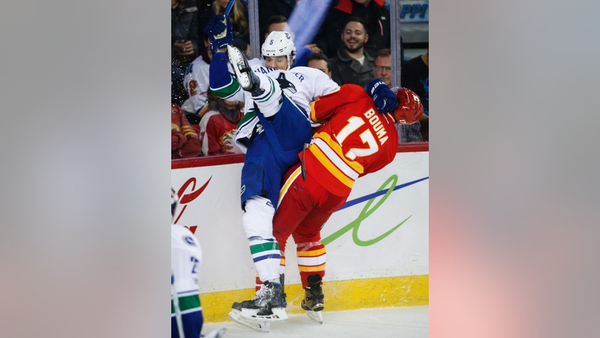 Vancouver Canucks' Luca Sbisa, left, of Italy, is checked by Calgary Flames' Lance Bouma during third-period NHL hockey game action in Calgary, Alberta, Saturday, Jan. 7, 2017. (Jeff McIntosh/The Canadian Press via AP)