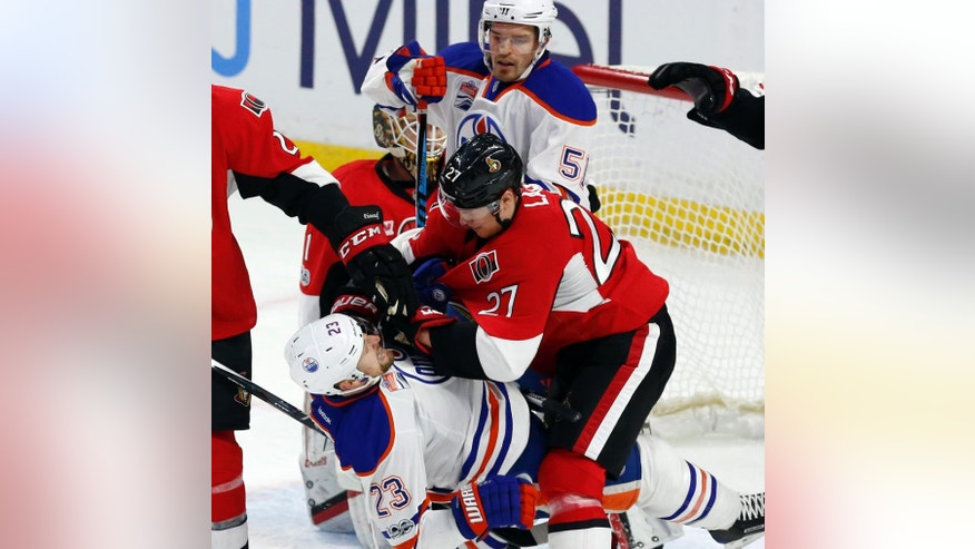 Ottawa Senators forward Curtis Lazar gets tangled up with Edmonton Oilers forward Matt Hendricks (23) in front of the Senators net during the first period of an NHL hockey game in Ottawa on Sunday, Jan. 8, 2017. (Fred Chartrand/The Canadian Press via AP)