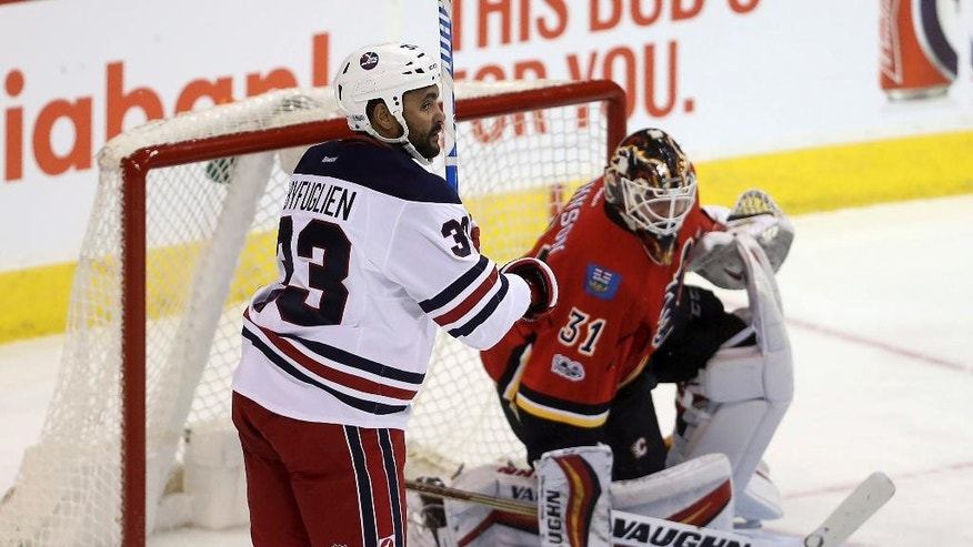 Winnipeg Jets defenseman Dustin Byfuglien (33) scores against Calgary Flames goalie Chad Johnson (31) during the first period of an NHL Hockey game Monday, Jan. 9, 2017, in Winnipeg, Manitoba. (Trevor Hagan/The Canadian Press via AP)