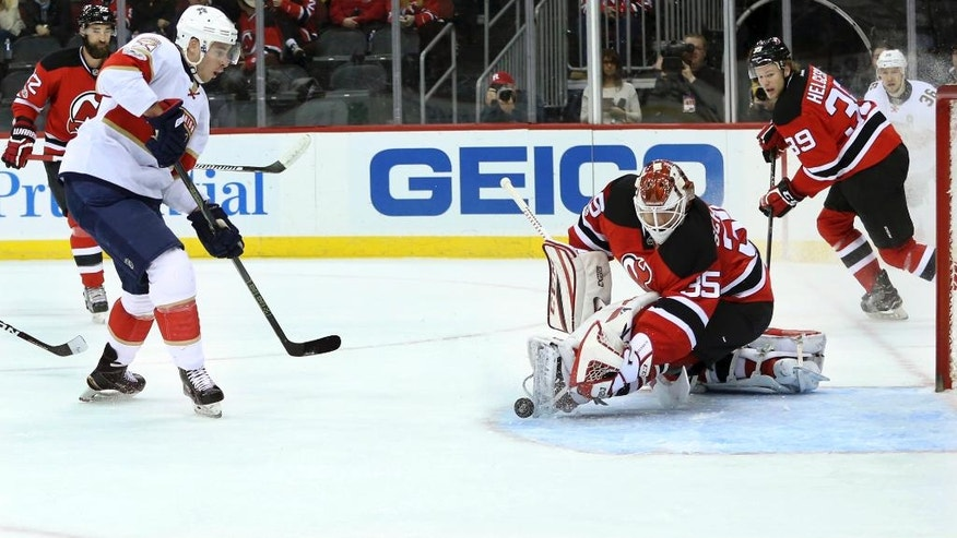 Florida Panthers right wing Reilly Smith (18) puts the puck into the net for a goal past New Jersey Devils goalie Cory Schneider (35) during the first period of an NHL hockey game Monday, Jan. 9, 2017, in Newark, N.J. (AP Photo/Mel Evans)