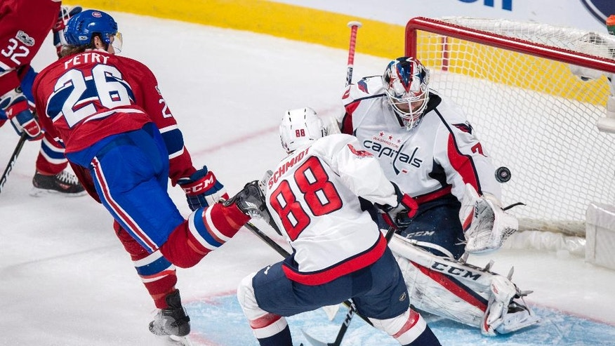 Washington Capitals goalie Braden Holtby (70) stops a shot by Montreal Canadiens defenseman Jeff Petry (26) as defenseman Nate Schmidt (88) watches during the second period of an NHL hockey game Monday, Jan. 9, 2017, in Montreal. (Paul Chiasson/The Canadian Press via AP)