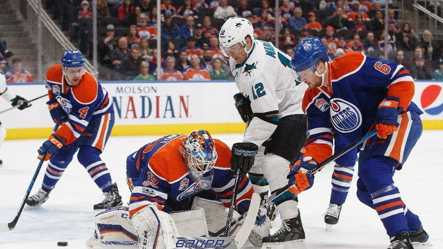 San Jose Sharks' Patrick Marleau (12) is stopped by Edmonton Oilers' goalie Cam Talbot (33) as Kris Russell (4) and Adam Larsson (6) look for the rebound during the first period of an NHL hockey game, Tuesday, Jan. 10, 2017 in Edmonton, Alberta.  (Jason Franson/The Canadian Press via AP)