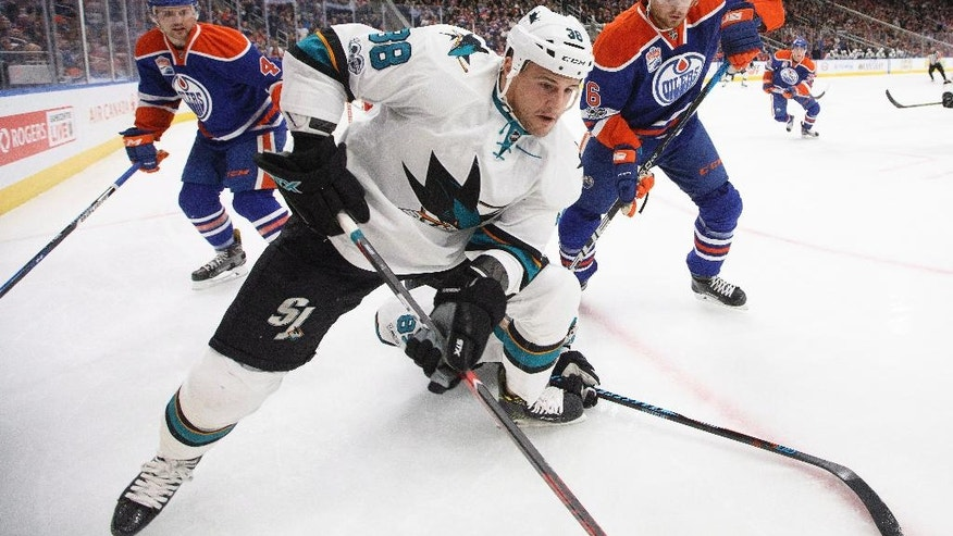 San Jose Sharks' Micheal Haley (38) and Edmonton Oilers' Adam Larsson (6) battle in the corner during the first period of an NHL hockey game, Tuesday, Jan. 10, 2017 in Edmonton, Alberta.  (Jason Franson/The Canadian Press via AP)