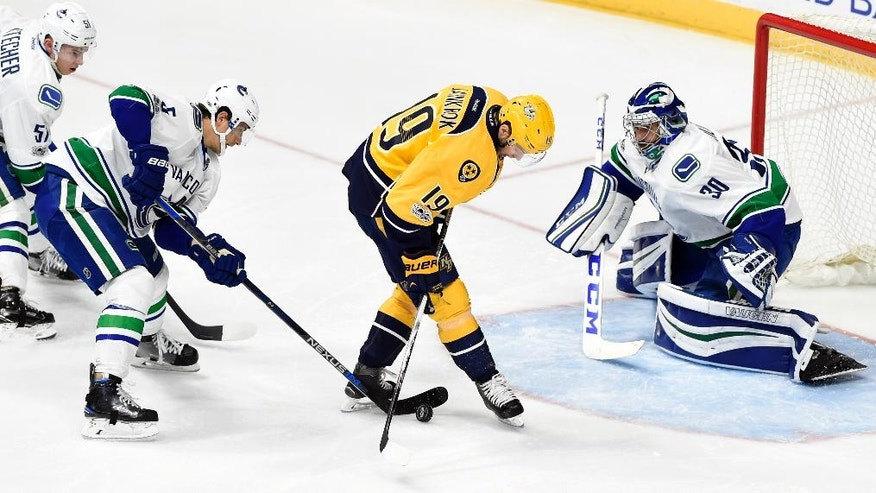 Vancouver Canucks defenseman Luca Sbisa (5), of Italy, knocks the puck away from Nashville Predators center Calle Jarnkrok (19), of Sweden, as goalie Ryan Miller (30) defends in net during the third period of an NHL hockey game Tuesday, Jan. 10, 2017, in Nashville, Tenn. The Predators won in overtime 2-1. (AP Photo/Mark Zaleski)