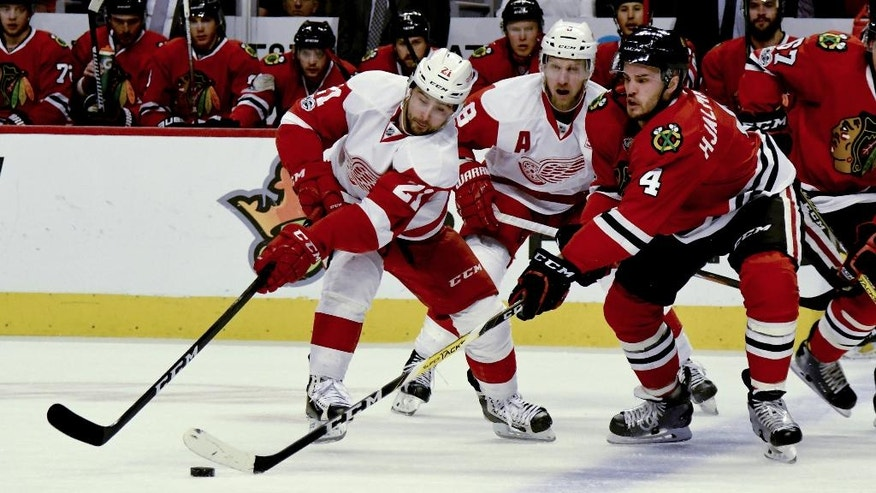 Detroit Red Wings left wing Tomas Tatar (21) and Chicago Blackhawks defenseman Niklas Hjalmarsson (4) compete for the puck as Detroit Red Wings left wing Justin Abdelkader, center, watches during the first period of an NHL hockey game on Tuesday, Jan. 10, 2017, in Chicago. (AP Photo/Matt Marton)