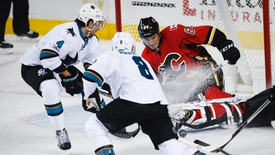 San Jose Sharks' Brenden Dillon, left, and Joe Pavelski, center, try to get a loose puck past Calgary Flames' Garnet Hathaway as he blocks the net, during the first period of an NHL hockey game Wednesday, Jan. 11, 2017, in Calgary, Alberta. (Jeff McIntosh/The Canadian Press via AP)