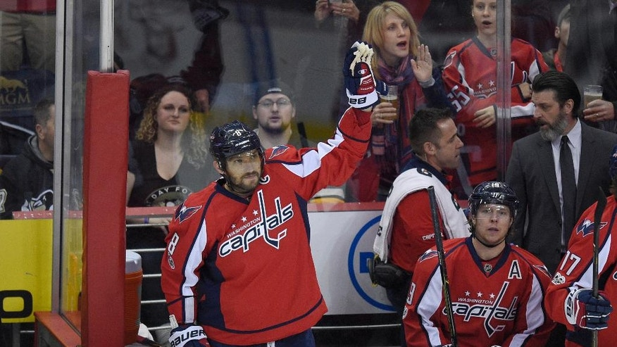 Washington Capitals left wing Alex Ovechkin (8), of Russia, waves to the crowd from the bench after he scored a goal during the first period of an NHL hockey game against the Pittsburgh Penguins, Wednesday, Jan. 11, 2017, in Washington.  Ovechkin didn't wait long to hit another milestone in his illustrious career, becoming the 84th player in NHL history to record 1,000 points.  (AP Photo/Nick Wass)