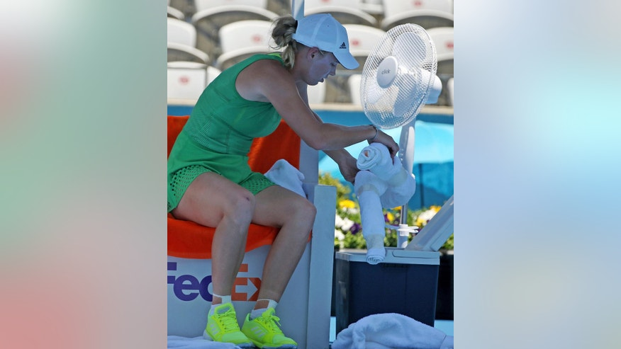 Caroline Wozniacki of Denmark places a damp towel into a cooler while using a fan during a break in play against Barbora Strycova of Czech Republic during their women's singles match at the Sydney International tennis tournament in Sydney Wednesday, Jan. 11, 2017. (AP Photo/Rick Rycroft)