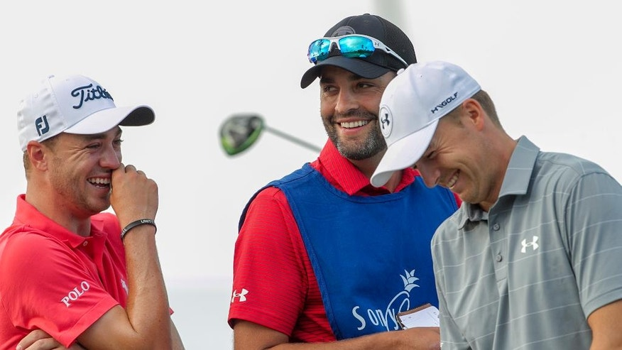 Justin Thomas, left, Michael Greller, center, and Jordan Spieth share a laugh on the 12th green during the first round of the Sony Open golf tournament, Thursday, Jan. 12, 2017, in Honolulu. Greller is Spieth's caddie for the tournament.(AP Photo/Marco Garcia)