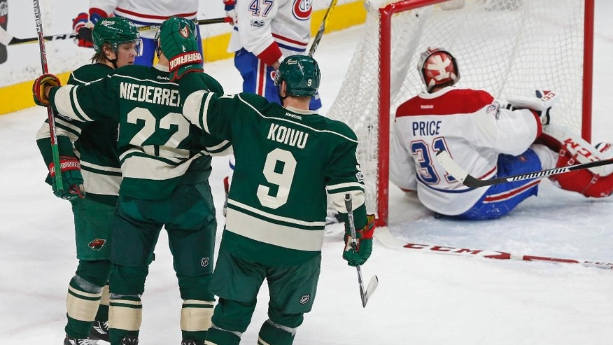 Montreal Canadiens goalie Carey Price, right, winds up sitting in goal after Minnesota Wild's Nino Niederreiter, second from left, of Switzerland, scored during the second period of an NHL hockey game Thursday, Jan. 12, 2017, in St. Paul, Minn. (AP Photo/Jim Mone)
