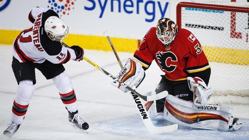 New Jersey Devils' P.A. Parenteau, left, has his shot kicked away by Calgary Flames goalie Chad Johnson during the first period of an NHL hockey game Friday, Jan. 13. 2017, in Calgary, Alberta. (Jeff McIntosh/The Canadian Press via AP)
