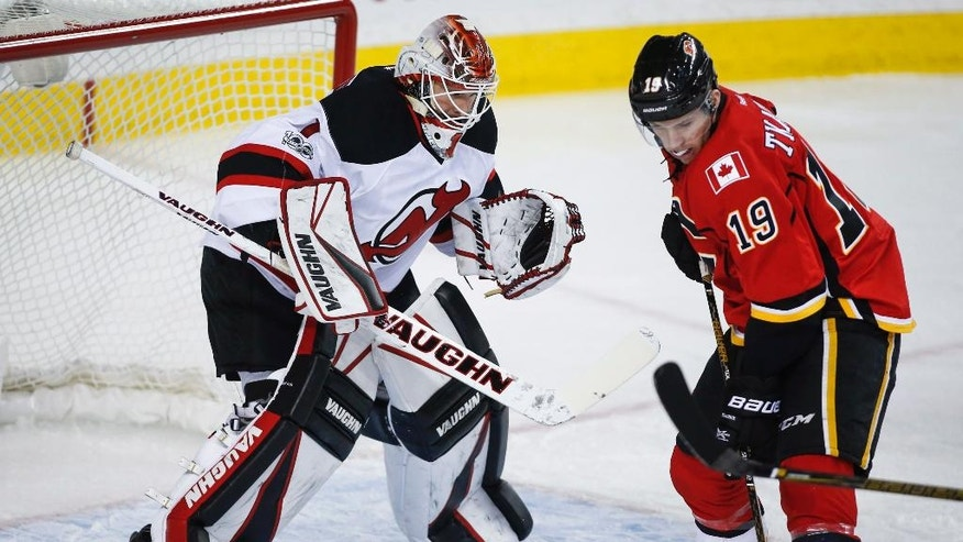 New Jersey Devils goalie Keith Kinkaid, left, watches as Calgary Flames' Matthew Tkachuk swats at a loose puck during the first period of an NHL hockey game Friday, Jan. 13. 2017, in Calgary, Alberta. (Jeff McIntosh/The Canadian Press via AP)