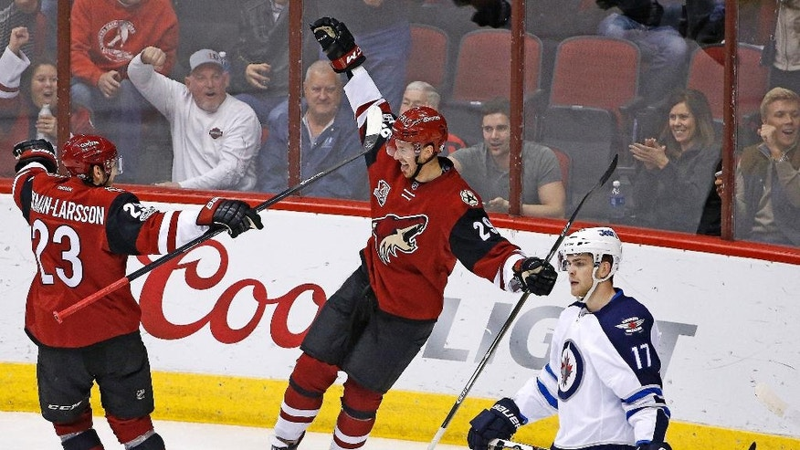 Arizona Coyotes left wing Brendan Perlini (29) celebrates a goal, his second during the first period of an NHL hockey game, with defenseman Oliver Ekman-Larsson (23) as Winnipeg Jets center Adam Lowry (17) skates away from the celebration Friday, Jan. 13, 2017, in Glendale, Ariz. (AP Photo/Ross D. Franklin)