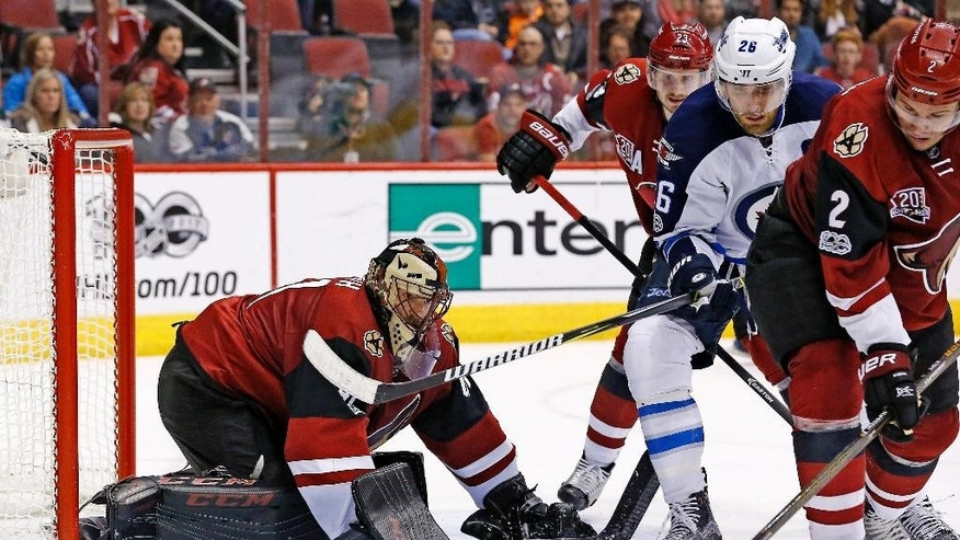 Arizona Coyotes goalie Mike Smith, left, makes a save on a shot as Winnipeg Jets right wing Blake Wheeler (26) battles for position with Coyotes defenseman Luke Schenn (2) and defenseman Oliver Ekman-Larsson (23) during the second period of an NHL hockey game Friday, Jan. 13, 2017, in Glendale, Ariz. (AP Photo/Ross D. Franklin)