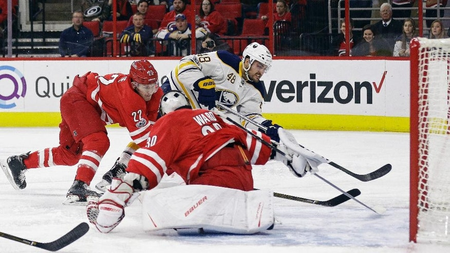 Buffalo Sabres' William Carrier (48) shoots and scores as Carolina Hurricanes goalie Cam Ward (30) and Brett Pesce (22) defend during the first period of an NHL hockey game in Raleigh, N.C., Friday, Jan. 13, 2017. (AP Photo/Gerry Broome)