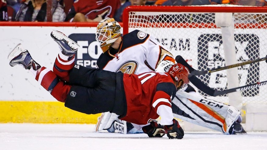 Anaheim Ducks goalie Jonathan Bernier (1) makes a save on a shot from a diving Arizona Coyotes left wing Anthony Duclair, right, during the first period of an NHL hockey game Saturday, Jan. 14, 2017, in Glendale, Ariz. (AP Photo/Ross D. Franklin)